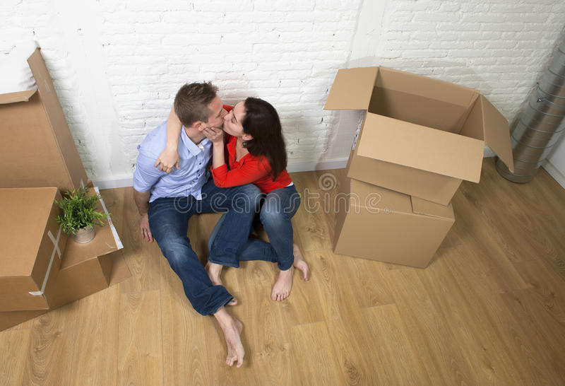 Happy American couple sitting on floor kissing celebrating moving in new house flat or apartment stock image