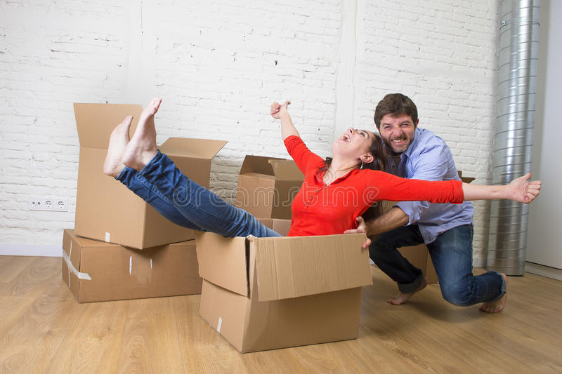 Happy American couple unpacking moving in new house playing with stock image