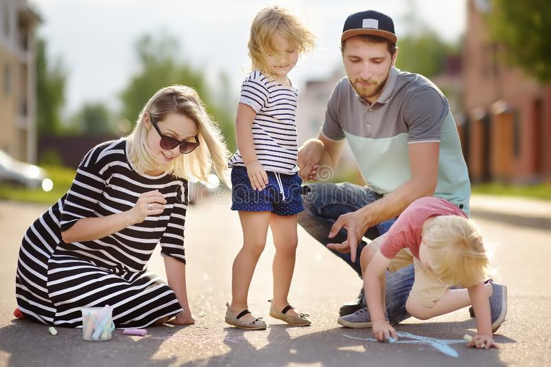 Happy amicable family with two children walking in summer. The word. `family` painted with colored chalk on asphalt.Creative leisure for children. Street art royalty free stock photo