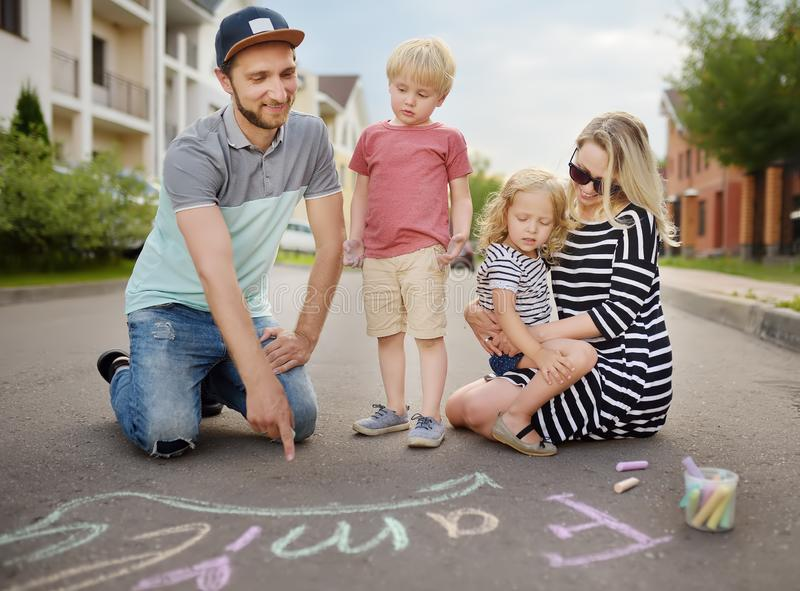 Happy amicable family with two children walking in summer. The word. `family` painted with colored chalk on asphalt.Creative leisure for children. Street art royalty free stock images