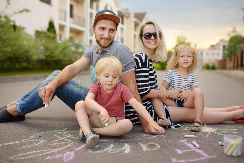 Happy amicable family with two children walking in summer. The word. `family` painted with colored chalk on asphalt.Creative leisure for children. Street art royalty free stock photography