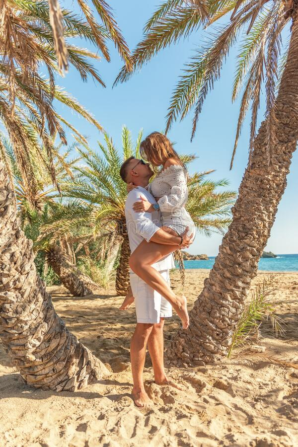 Happy amorous couple hugging on a tropical beach under the palm tree. Summer love concept.  royalty free stock image