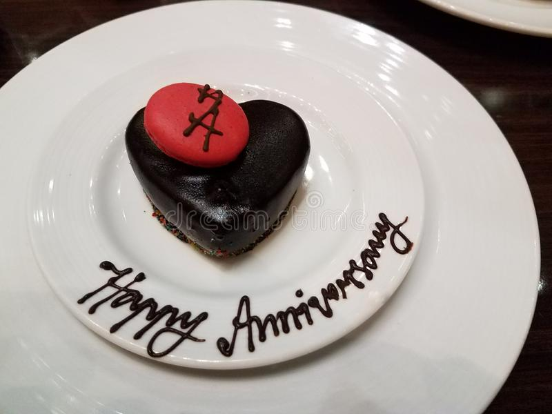 Happy Anniversary. Anniversary cake with red cookie on white serving plates stock photos