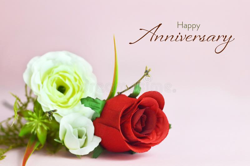Happy Anniversary card. Artificial flowers on pink background stock photo