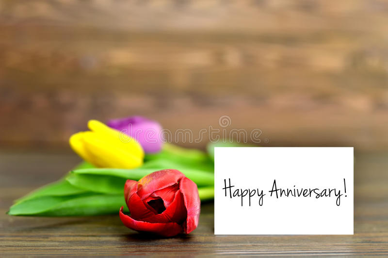 Happy Anniversary card and colorful tulips. Wooden background stock photos