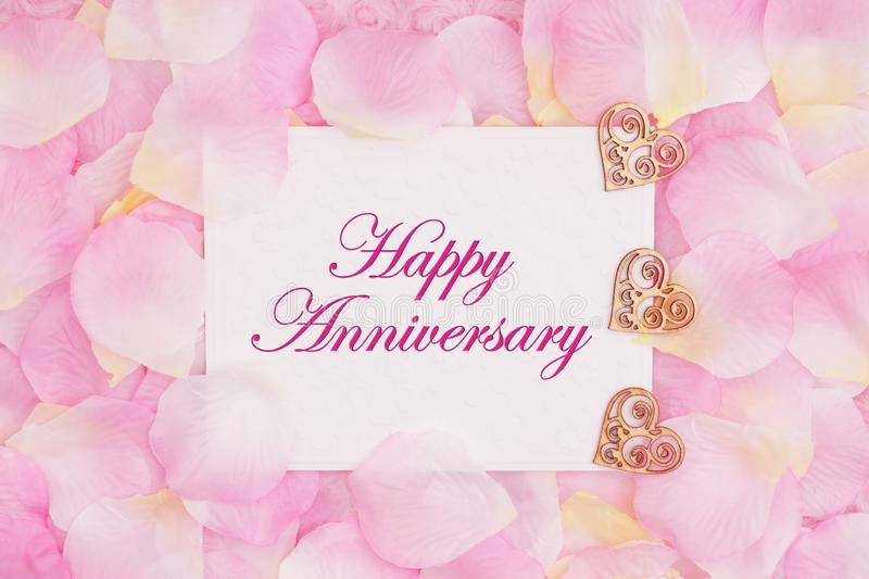 Happy Anniversary greeting card with hearts. Happy Anniversary greeting card with wood hearts and rose flower petals royalty free stock images