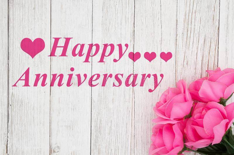Happy Anniversary Greeting with roses. Happy Anniversary greeting with pink roses on a weathered whitewash wood background royalty free stock images