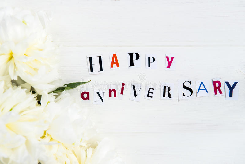 Happy Anniversary Letters Cut out from Magazines and White Peonies. Nearby, white background royalty free stock photography