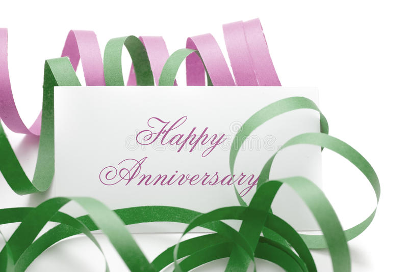 Happy anniversary message on a card. Happy anniversary message - card with green and pink cotillions isolated on a white background stock photography