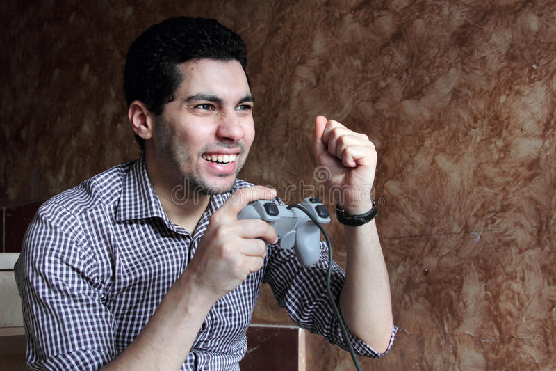 Happy arab egyptian businessman playing playstation royalty free stock image