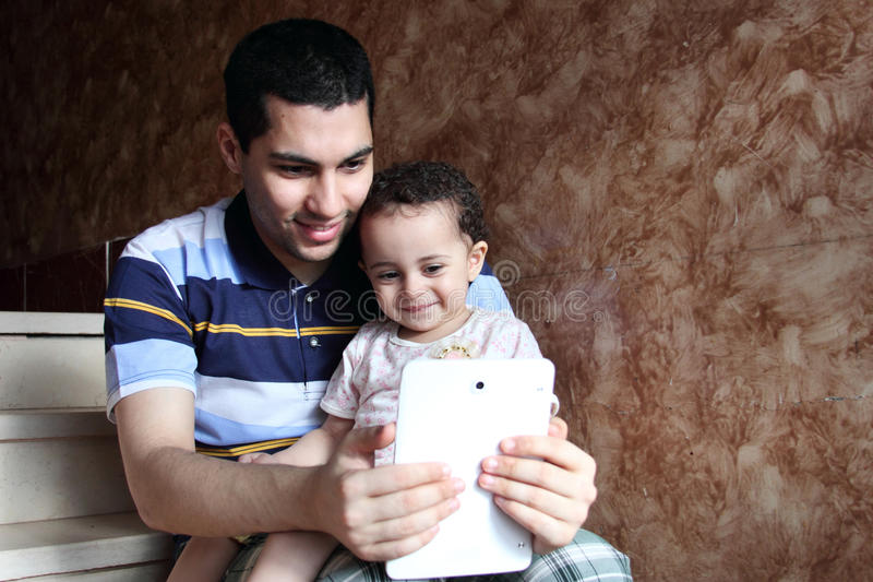 Happy arab egyptian father with daughter taking selfie stock image