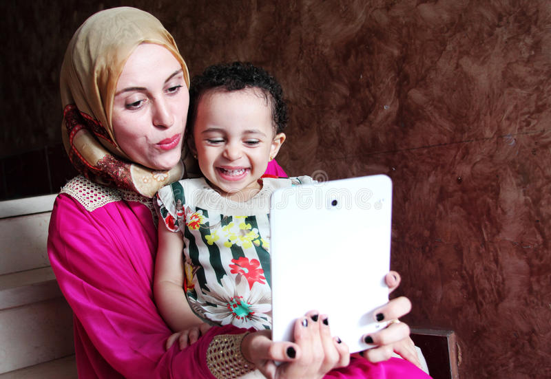 Happy arab muslim mother with her baby girl taking selfie stock images