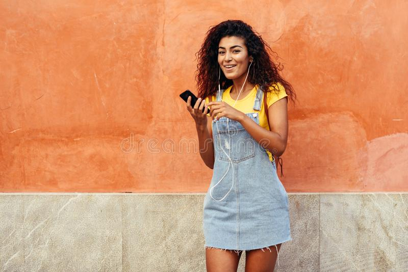 Happy Arab woman listening to music with earphones against red wall stock photo