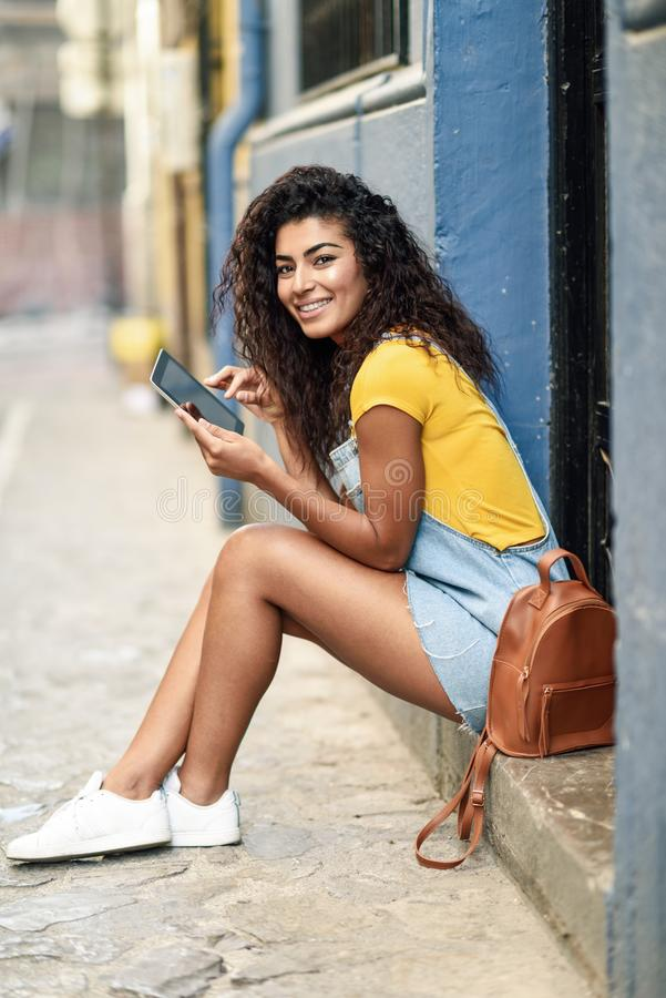 Happy Arab woman sitting on urban step with a digital tablet stock image