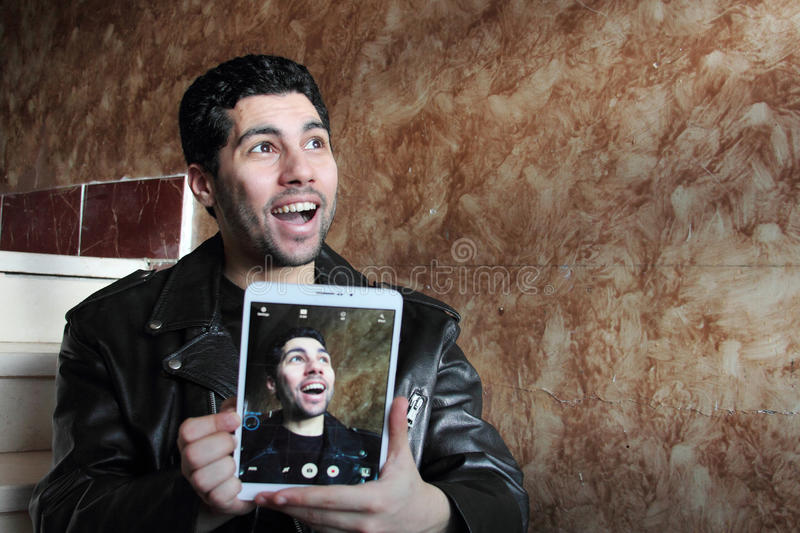 Happy arab young businessman in jacket taking selfie stock image