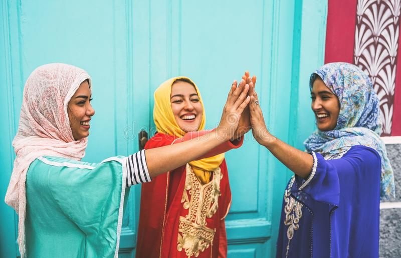 Happy Arabian women stacking hands together outdoor - Young Muslim girls having fun in the university royalty free stock photos