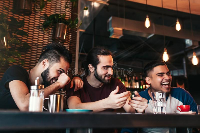 Happy arabian young men hanging in loft cafe. Group of mixed race people having fun in lounge bar. Friends chilling out and laughing stock image