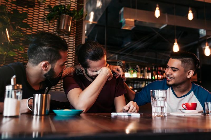 Happy arabian young men hanging in loft cafe. Group of mixed race people having fun in lounge bar. Friends chilling out and laughing stock photo