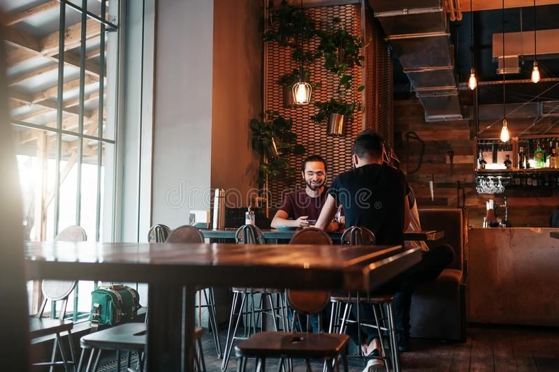 Happy arabian young men hanging in loft cafe. Group of mixed race people talking in lounge bar. Friends chilling out and relaxing royalty free stock photo