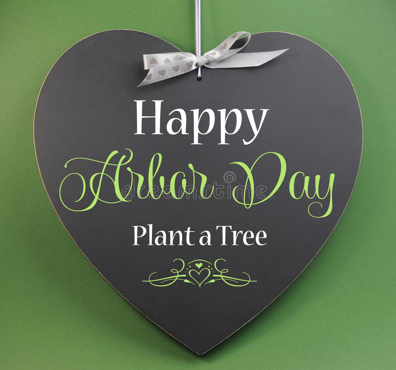 Happy Arbor Day, Plant a Tree, greeting message sign on heart shaped blackboard royalty free stock photo