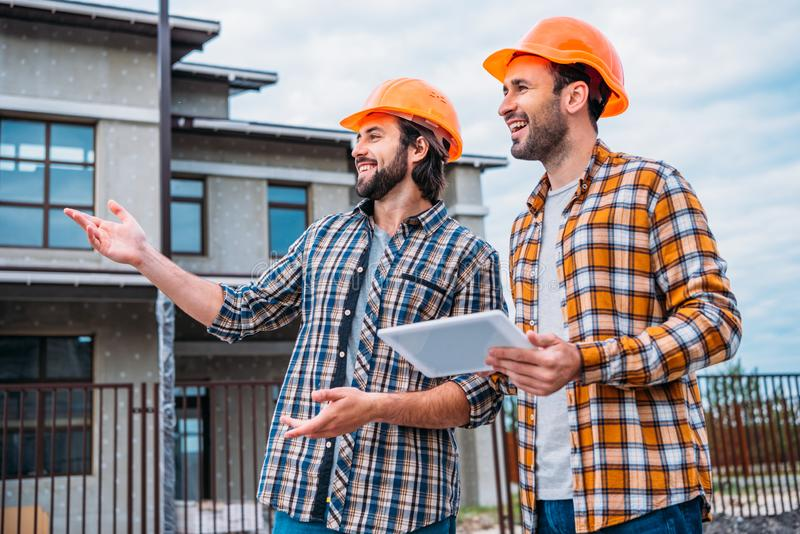Happy architects with digital tablet pointing. At construction site royalty free stock images