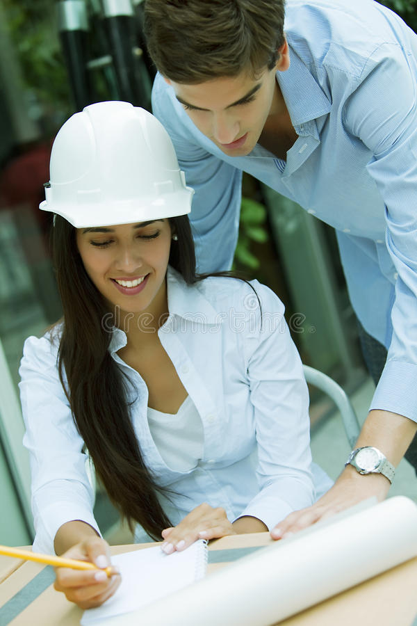 Happy architects working. Outdoors with helmet stock photography