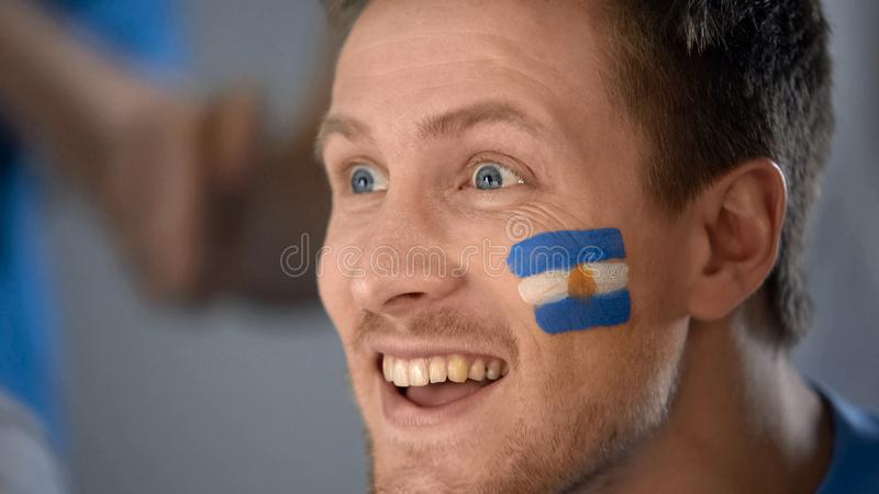 Happy Argentina fan watching game on tv, celebrating victory in match, closeup. Stock photo royalty free stock photos