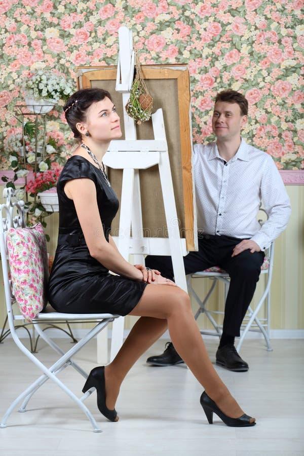Happy artist paints portrait of pretty woman. Happy artist paints portrait of pretty women in beautiful retro interior. Focus on woman stock photo