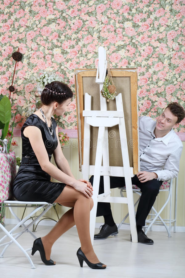 Happy artist peeks out from behind his easel on pretty woman. Happy artist peeks out from behind his easel on pretty women in beautiful retro interior. Focus on stock photography