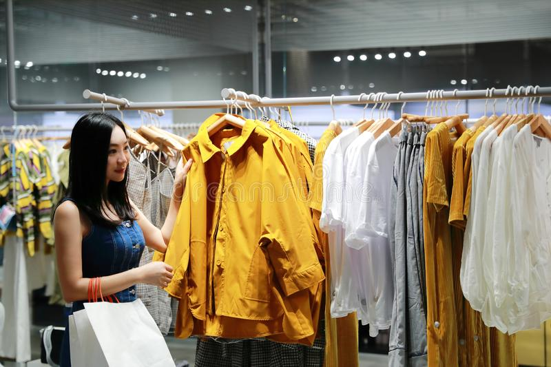 Happy Asia Chinese Eastern oriental young trendy woman girl shopping in mall with bags pick out clothes. Woman buying pretty beautiful dress clothes in shopping royalty free stock photos