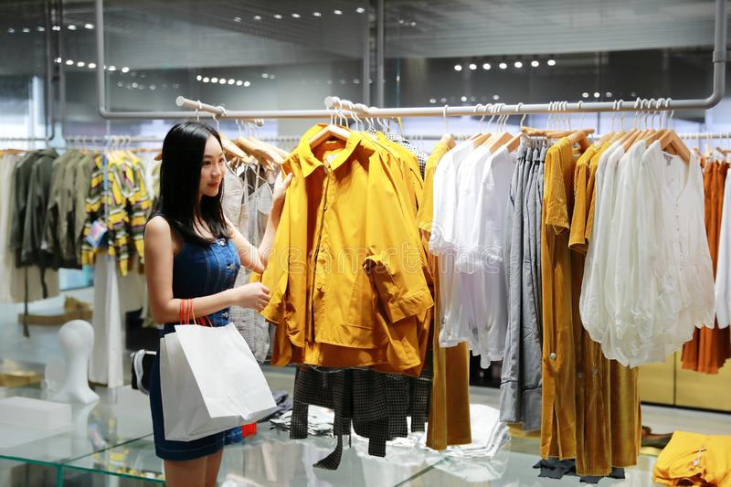 Happy Asia Chinese Eastern oriental young trendy woman girl shopping in mall with bags pick out clothes. Woman buying pretty beautiful dress clothes in shopping royalty free stock image