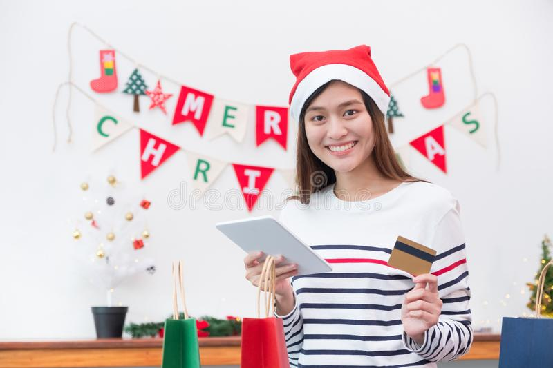 Happy Asia woman use credit card buy Christmas gift with mobile. Apps at home in party,Holiday online shopping, Mobile banking payment stock photos