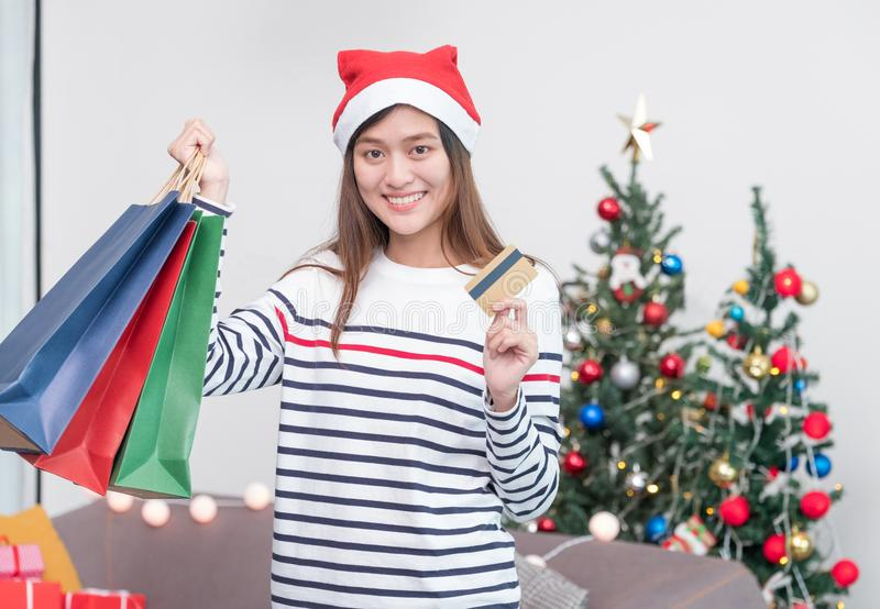 Happy Asia woman use credit card buy Christmas gift in shopping. Bag at home in party,Holiday online shopping royalty free stock photo