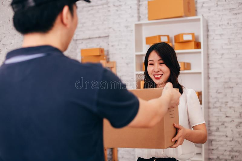 Happy Asian adult business female in the office receiving a parcel from male deliverman stock photography