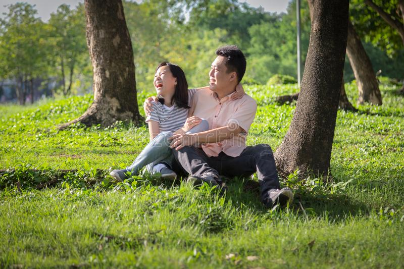 Happy asian adult man and cute child girl with love,hugging and smiling in summer nature,father and little beautiful daughter stock photography