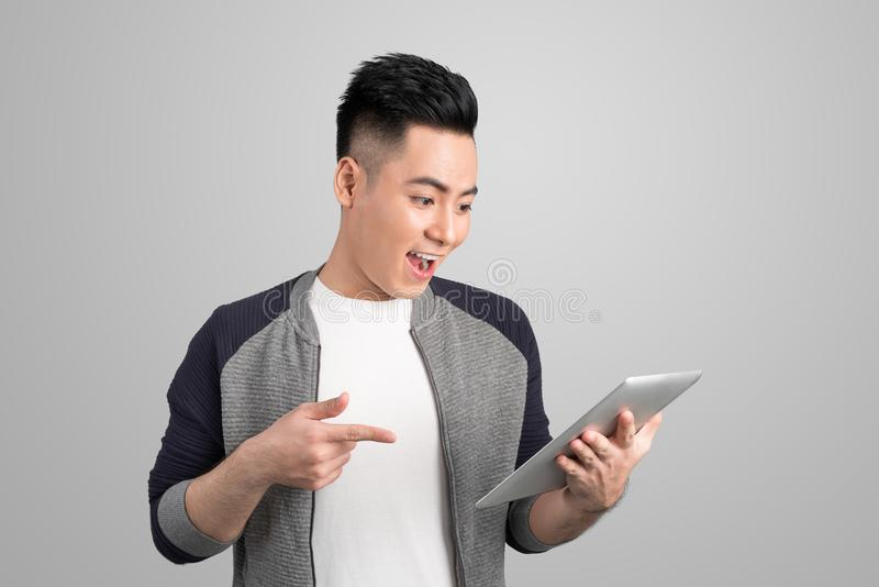 Happy asian attractive young man standing and pointing tablet over grey background stock photos