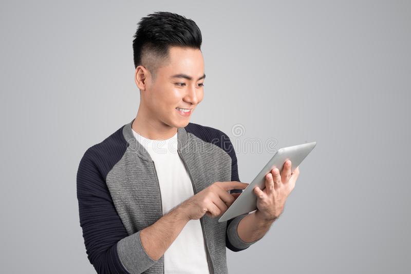 Happy asian attractive young man standing and touching tablet over grey background stock image