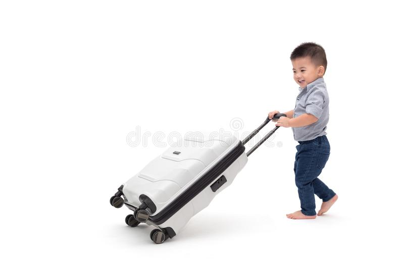 Happy Asian baby boy sliding luggage travel bag. Or suitcase  on white background, Traveling and new adventures family trip for child passenger concept, One royalty free stock photos