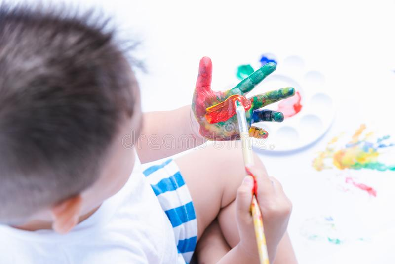 Happy asian baby child use paintbrush draw water color or fingerpaint on hand royalty free stock photos