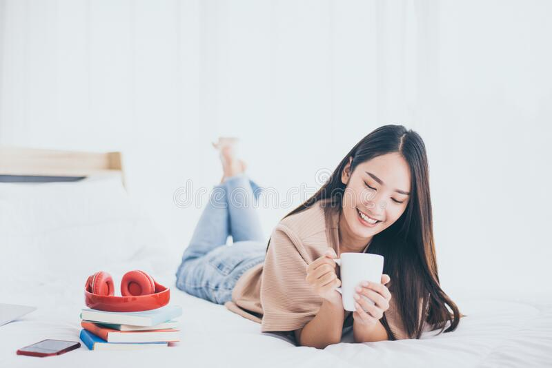 Happy asian beautiful woman drinking coffee on the bed in home royalty free stock photos
