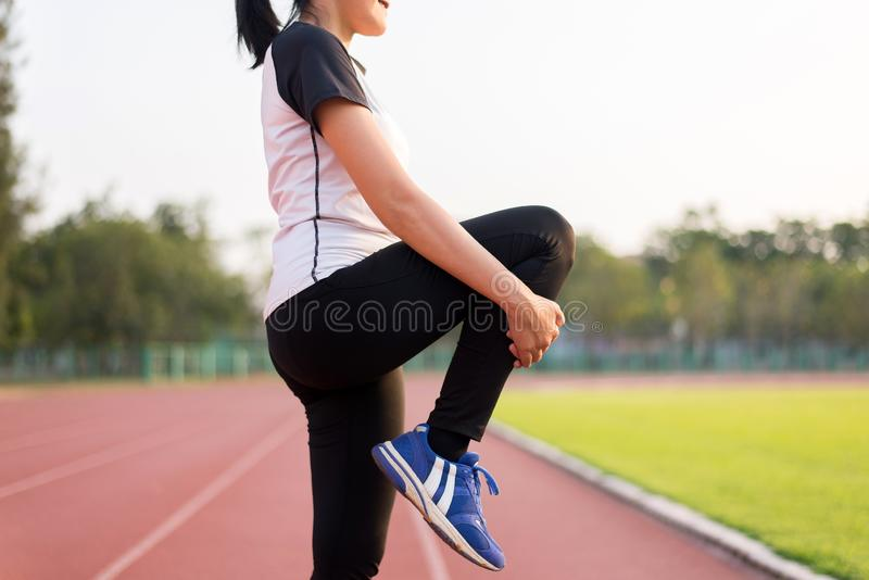 Happy asian beautiful women stretching and warming up before running or working out at track outdoor in the evening. Happy asian beautiful woman stretching and stock images