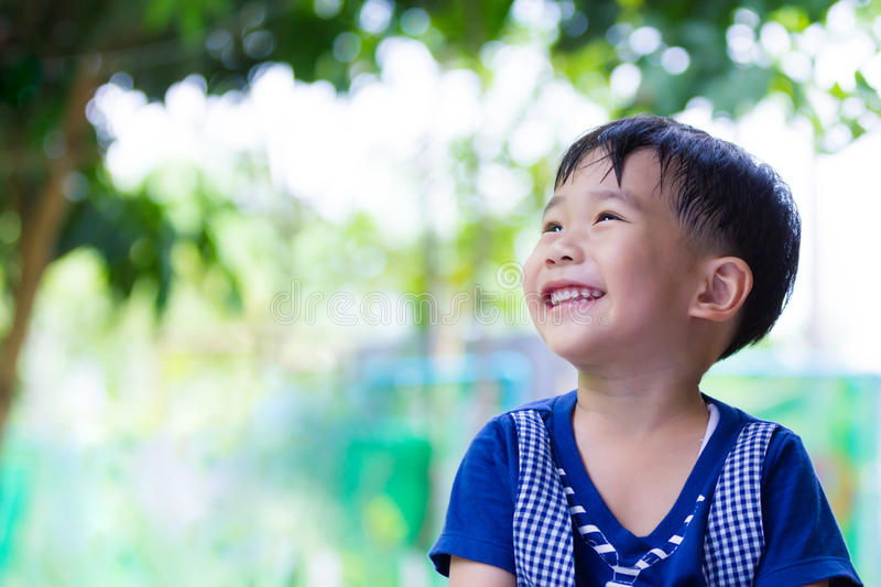 Happy asian boy looking up at park. Outdoors in the day time, tr stock images