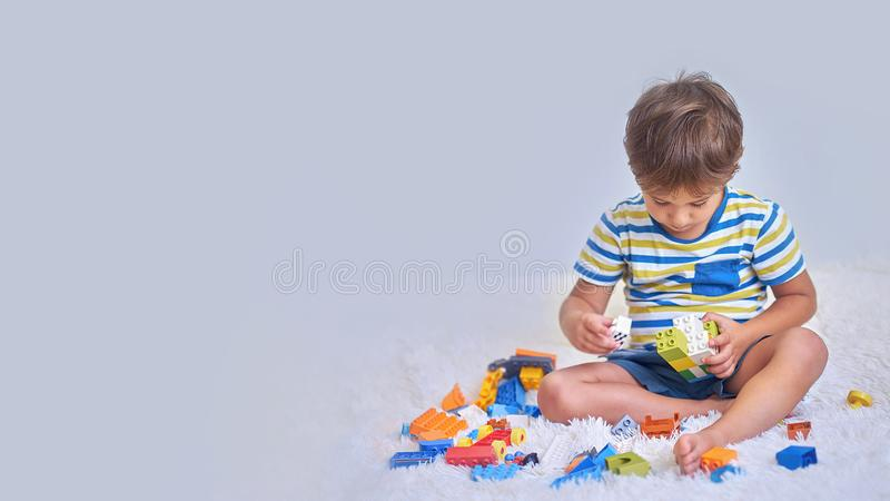Happy asian boy playing with colorful construction plastic blocks on white Bed at home. royalty free stock photos