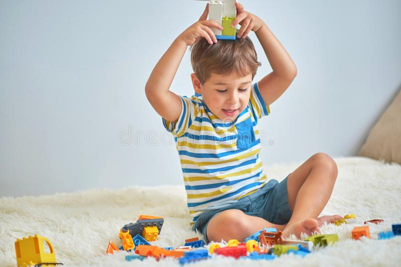 Happy asian boy playing with colorful construction plastic blocks on white Bed at home. royalty free stock photography