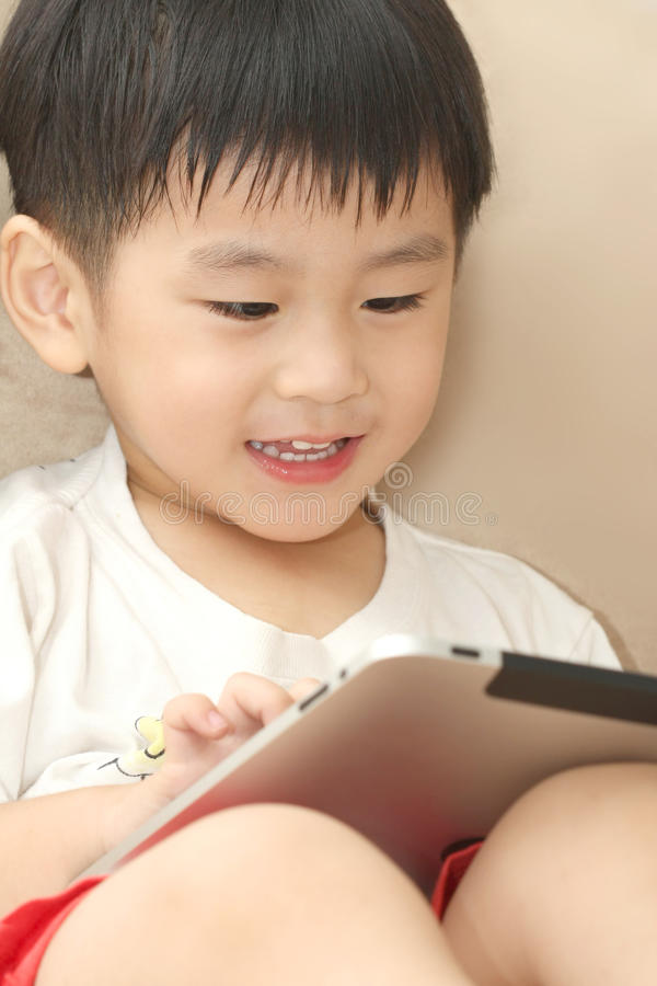 Happy Asian boy playing iPad stock photos