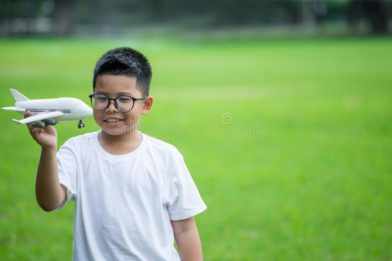 Happy asian boy playing with toy plastic airplane in park outdoors.kid dreams of journey royalty free stock photo