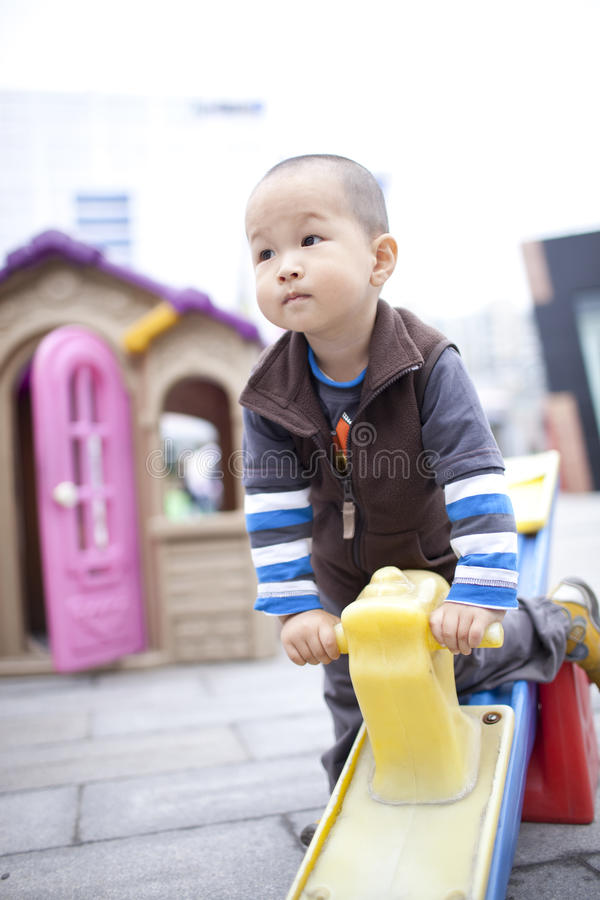 Happy asian boy sitting on the seesaw stock photography