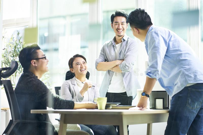 Happy asian business team meeting in office. Group of four happy young asian corporate people teammates meeting discussing business in office royalty free stock photography
