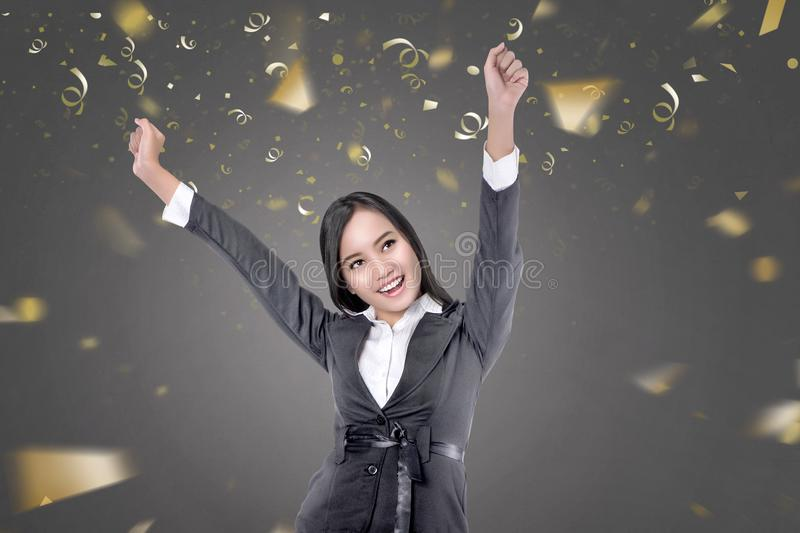 Happy asian business woman with confetti. On black background stock photo