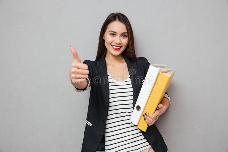 Happy asian business woman holding folders and showing thumb up royalty free stock images